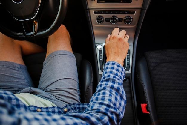 Mężczyzna w szortach i koszuli siedzi przy kierownicy, trzymając skrzynię biegów