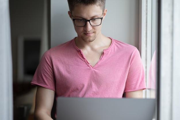 Mężczyzna w szortach i różowej koszulce siedzi na oknie i pracuje na laptopie