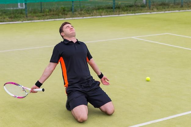 Mężczyzna w tenisa ubrany w strój sportowy siedzi na kolanach z powodu przegranego meczu tenisowego na boisku z zieloną trawą