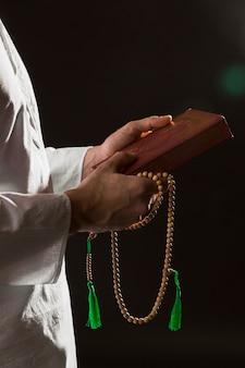 Mężczyzna w tradycyjnych arabskich ubraniach trzyma koran i modlitewne koraliki