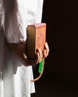 Mężczyzna w tradycyjnych arabskich ubraniach trzyma za plecami koran