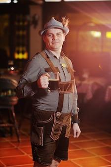 Mężczyzna w tradycyjnym bawarskim stroju na oktoberfest z piwem w ręku uśmiecha się na powierzchni pubu