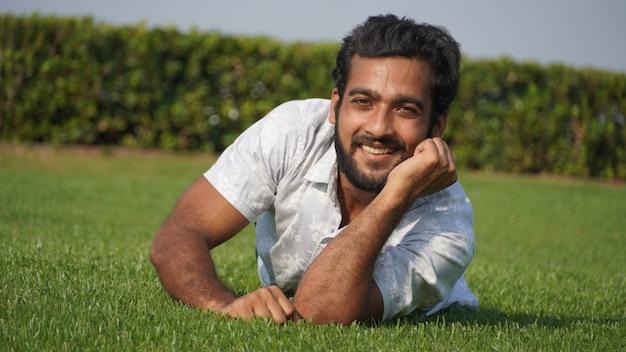 Mężczyzna w trawie i uśmiechnięty