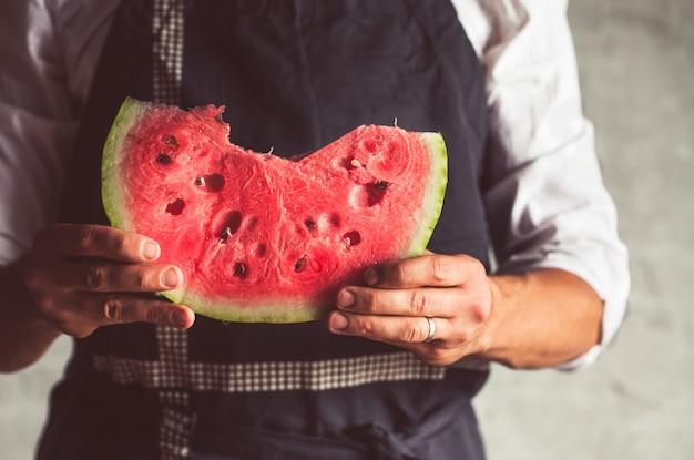 Mężczyzna w trzymającym duży kawałek arbuza w paski. dojrzała pyszna jagoda. zabytkowe produkty rolne. zdrowy produkt.