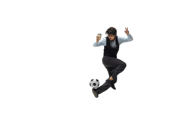Mężczyzna w ubraniach biurowych grający w piłkę nożną lub piłkę nożną z piłką na białym tle nietypowy wygląd