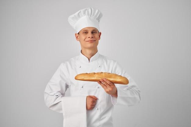 Mężczyzna w ubraniach szefa kuchni, trzymający profesjonalistę piekarza bochenka
