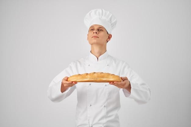 Mężczyzna w ubraniach szefów kuchni profesjonalnie z bagietką w rękach świeży produkt działa