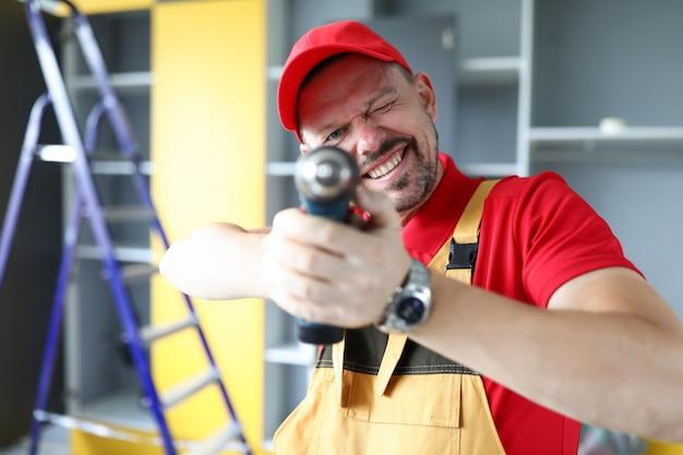 Mężczyzna w ubraniu roboczym celuje w śrubokręt i uśmiecha się stolarz montuje meble w domu