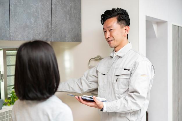 Mężczyzna w ubraniu roboczym wyjaśnia kobiecie w kuchni