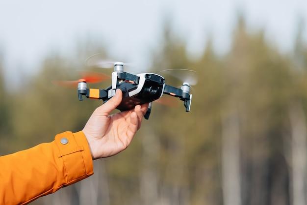 Mężczyzna w ubraniu z pomarańczowym rękawem trzyma w dłoni latającego drona quadkoptera.