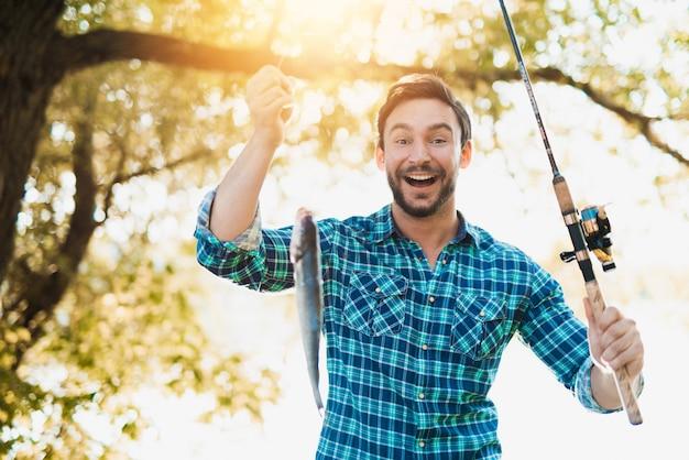 Mężczyzna w w kratkę koszula łowić na rzece w lecie.