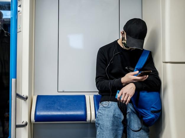 Mężczyzna w wagonie metra z entuzjazmem spogląda na swój smartfon. pasażer ma na twarzy ochronną maskę medyczną. druga fala koronawirusa.