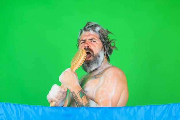 Mężczyzna w wannie mężczyzna weź kąpiel szczotka do kąpieli mycie ciała brodaty mężczyzna mycie włosów pielęgnacja spa prysznic