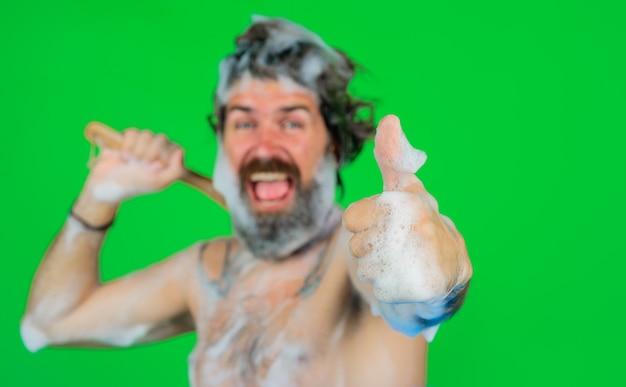 Mężczyzna w wannie pokazuje kciuk w górę mężczyzna bierze kąpiel mężczyzna z pianką na głowie szczotka do kąpieli mycie ciała brodaty mężczyzna