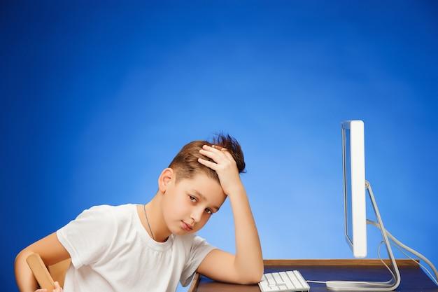 Mężczyzna w wieku szkolnym siedzi przed monitorem ekranu
