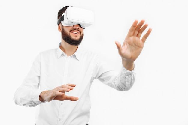 Mężczyzna w wirtualnych okularach naciska palec na pustą przestrzeń na białej ścianie