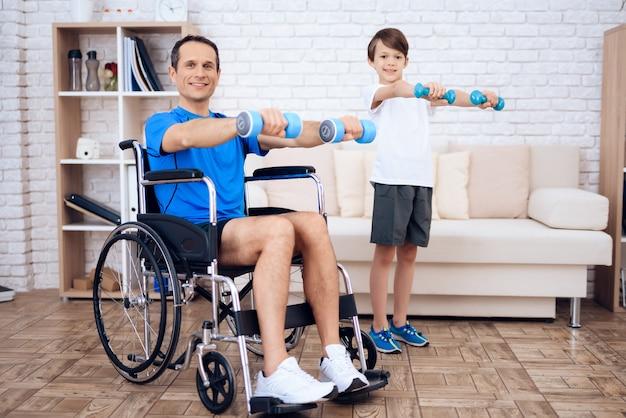 Mężczyzna w wózku inwalidzkim i synu z dumbbells w rękach.