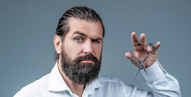 Mężczyzna w zakładzie fryzjerskim, strzyżenie, golenie. brodaty mężczyzna na białym tle na szarym tle. mans fryzura w fryzjera. nożyczki fryzjerskie, salon fryzjerski