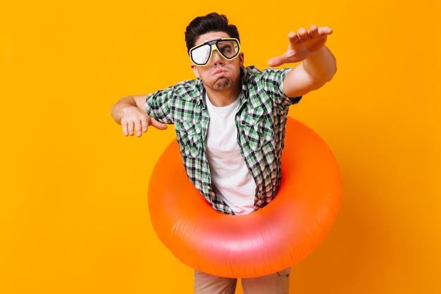 Mężczyzna w zielonej koszuli, masce do nurkowania i nadmuchiwanym kółku przedstawia pływanie na pomarańczowej przestrzeni.