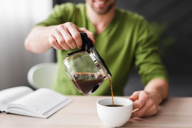 Mężczyzna w zielonej koszuli nalewanie kawy z bliska