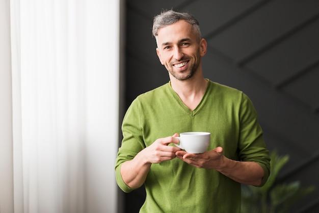 Mężczyzna w zielonej koszuli trzyma białą filiżankę kawy i uśmiecha się