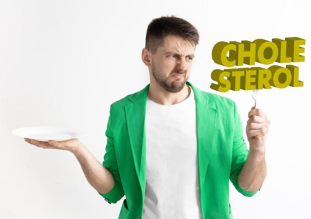 Mężczyzna w zielonej kurtce z ludem na białym tle. męski model trzymający talerz z literami słowa cholesterol. wybór zdrowego odżywiania, diety, żywienia ekologicznego i stylu życia przyjaznego naturze.