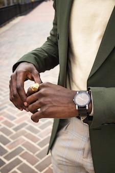 Mężczyzna w zielonej marynarce, noszący złoty pierścionek z lwem i zegarek