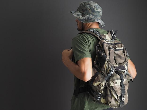 Mężczyzna w zielonym kamuflażu z plecakiem kamuflażu na szarym tle.