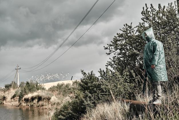 Mężczyzna w zielonym płaszczu przeciwdeszczowym na brzegu w pobliżu wody.