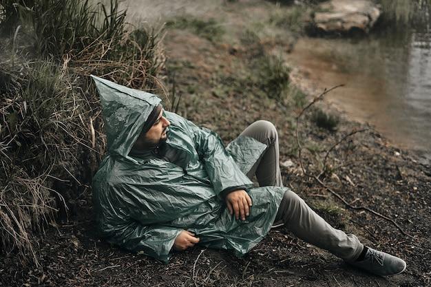 Mężczyzna w zielonym płaszczu przeciwdeszczowym siedzi na ziemi w naturze