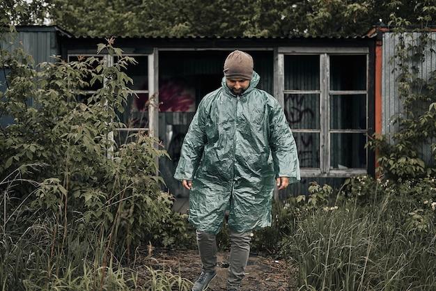Mężczyzna w zielonym płaszczu przeciwdeszczowym w pobliżu opuszczonego drewnianego domu.