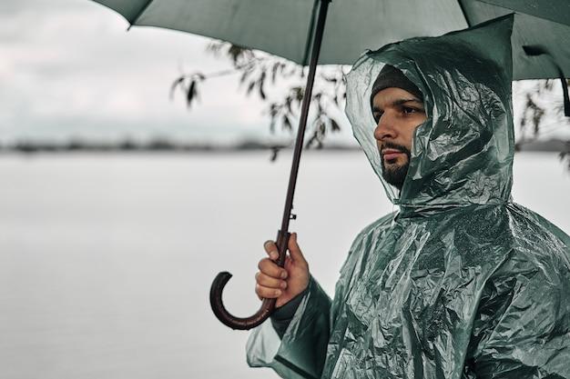 Mężczyzna w zielonym płaszczu przeciwdeszczowym z parasolem na brzegu w pobliżu wody.