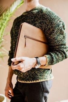 Mężczyzna w zielonym swetrze niosący torbę na laptopa