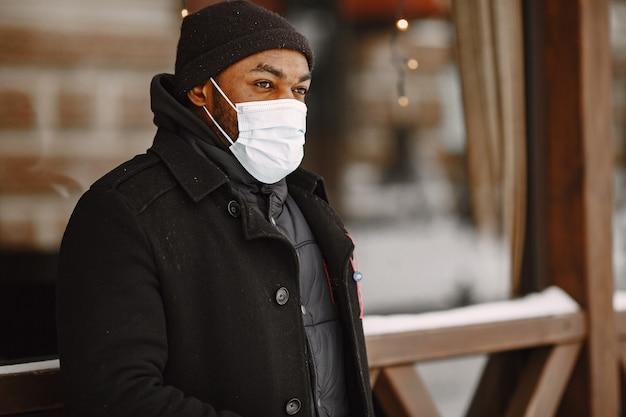 Mężczyzna w zimowym miasteczku. facet w czarnym płaszczu. mężczyzna w masce medycznej.