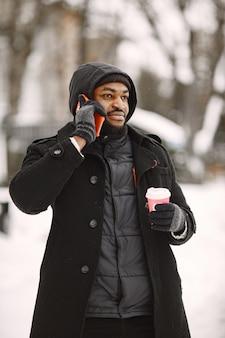 Mężczyzna w zimowym miasteczku. facet w czarnym płaszczu. mężczyzna z kawą i telefonem.
