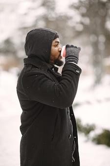 Mężczyzna w zimowym miasteczku. facet w czarnym płaszczu. mężczyzna z kawą.