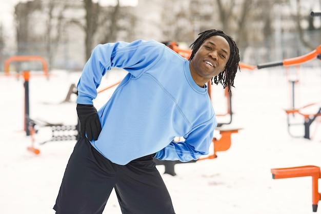 Mężczyzna w zimowym parku. afrykanin trenujący na zewnątrz.