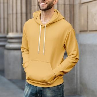 Mężczyzna w żółtej bluzie z kapturem streetwear moda odzież męska