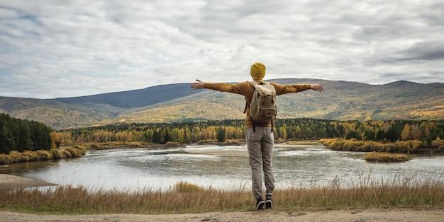 Mężczyzna w żółtej czapce i swetrze z plecakiem stoi na drodze z wyciągniętymi na boki rękoma przed rzeką, jesiennym złotym lasem i wzgórzami
