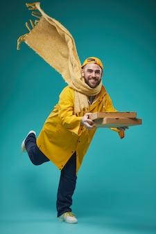 Mężczyzna w żółtej dostarczającej pizzy