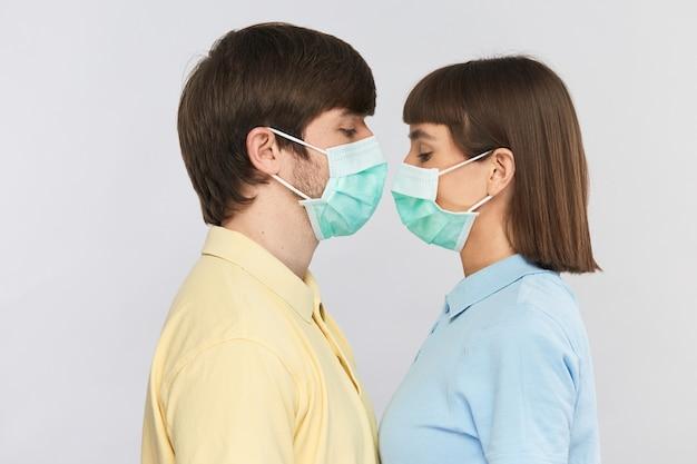 Mężczyzna w żółtej koszuli i kobieta w niebieskiej koszuli noszą sterylną maskę i patrzą w dół stojąc twarzą w twarz, maska ochronna na ludziach podczas covid-19
