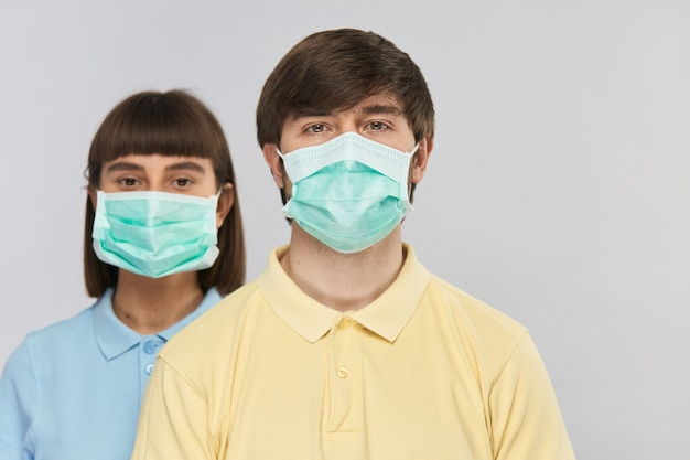 Mężczyzna w żółtej koszuli i masce oddechowej patrząc na kamery i dziewczyna w masce ochronnej z tyłu, izolacja wirusa koronowego, miejsce na kopię
