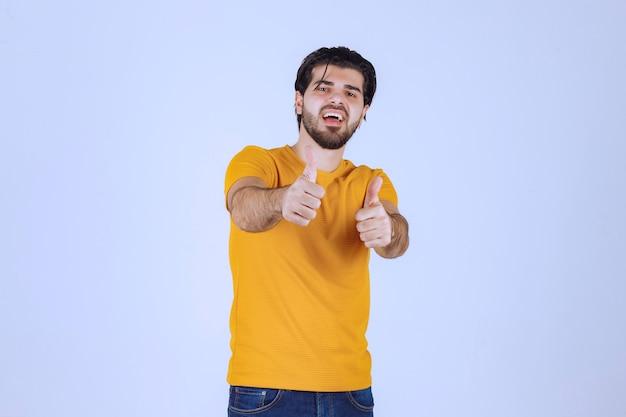 Mężczyzna w żółtej koszuli pokazujący kciuk w górę