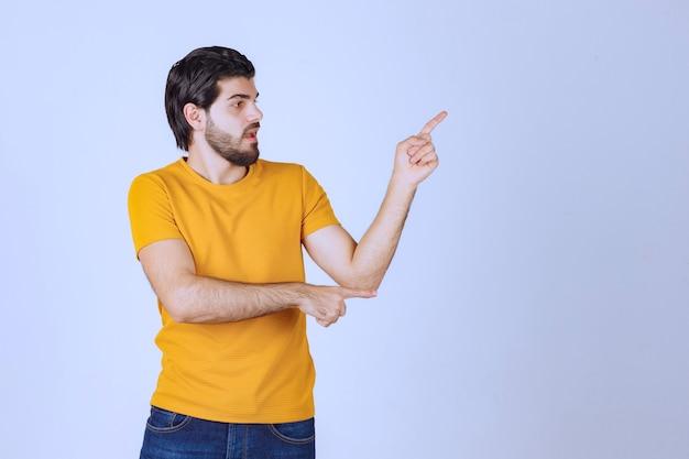Mężczyzna w żółtej koszuli pokazuje coś po prawej stronie.