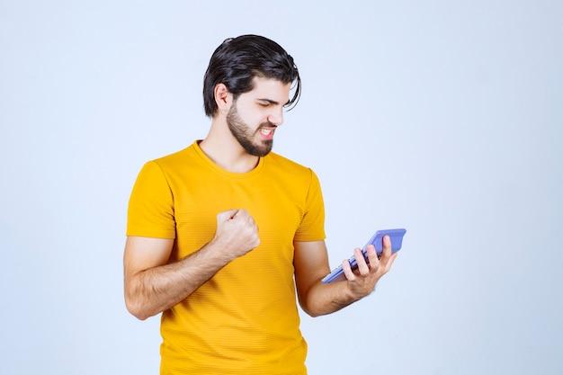 Mężczyzna w żółtej koszuli pracuje z kalkulatorem i wygląda na szczęśliwego z powodu wyników.