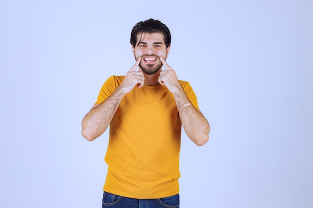 Mężczyzna w żółtej koszuli przykłada rękę do twarzy i się śmieje