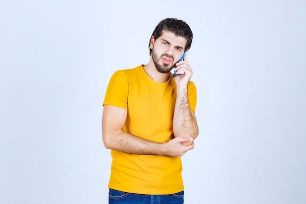 Mężczyzna w żółtej koszuli rozmawia przez telefon.