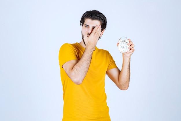 Mężczyzna w żółtej koszuli trzyma budzik i wygląda sennie.