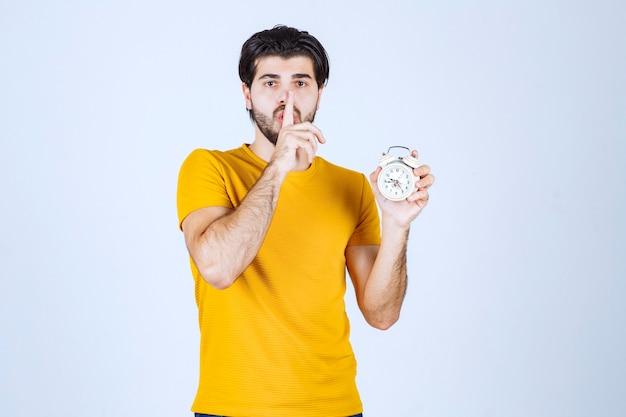Mężczyzna w żółtej koszuli trzymający budzik i wykonujący gest ciszy