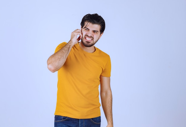 Mężczyzna w żółtej koszuli wygląda na przestraszonego i zachwyconego